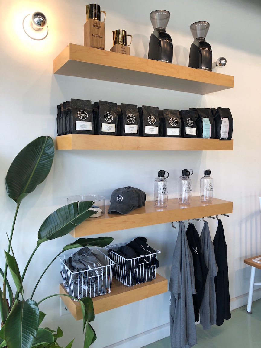 Shelving with shirts, stickers, and pour over coffee machines for sale