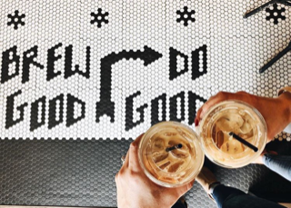 "Tiles on the floor spelling out ""brew good, do good"""