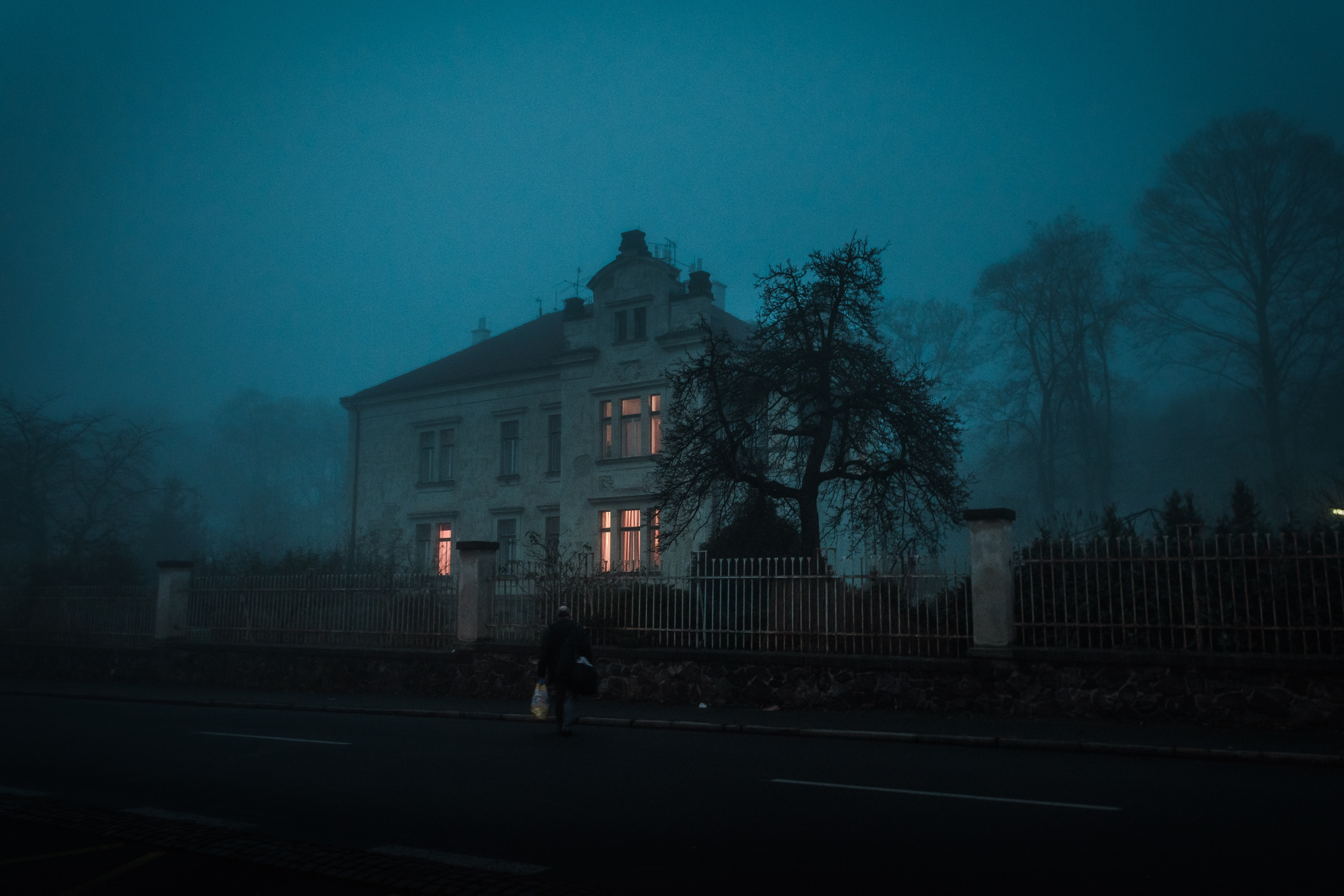 Picture of a house at dusk, surrounded by fog