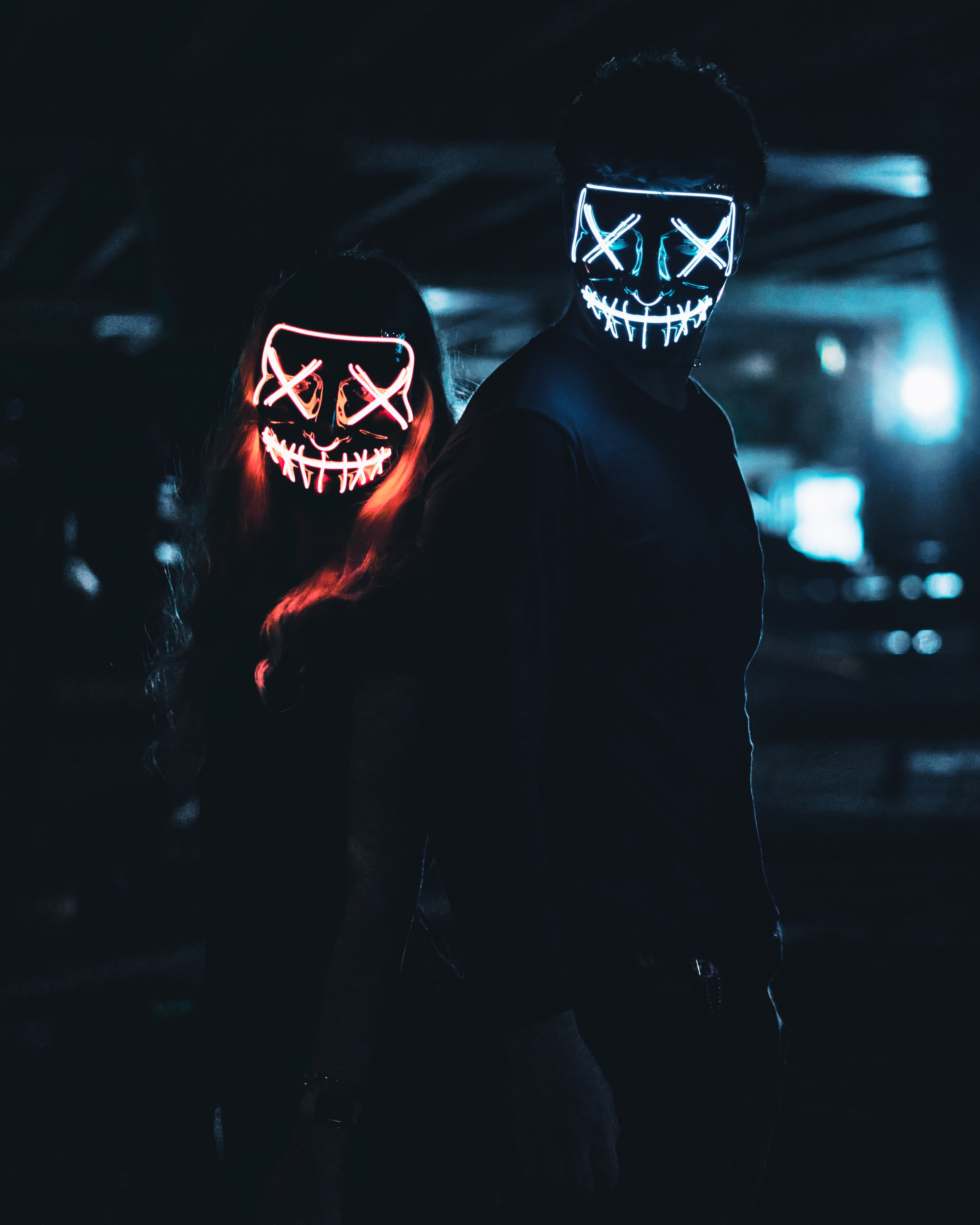 Two people with light-up scary face masks