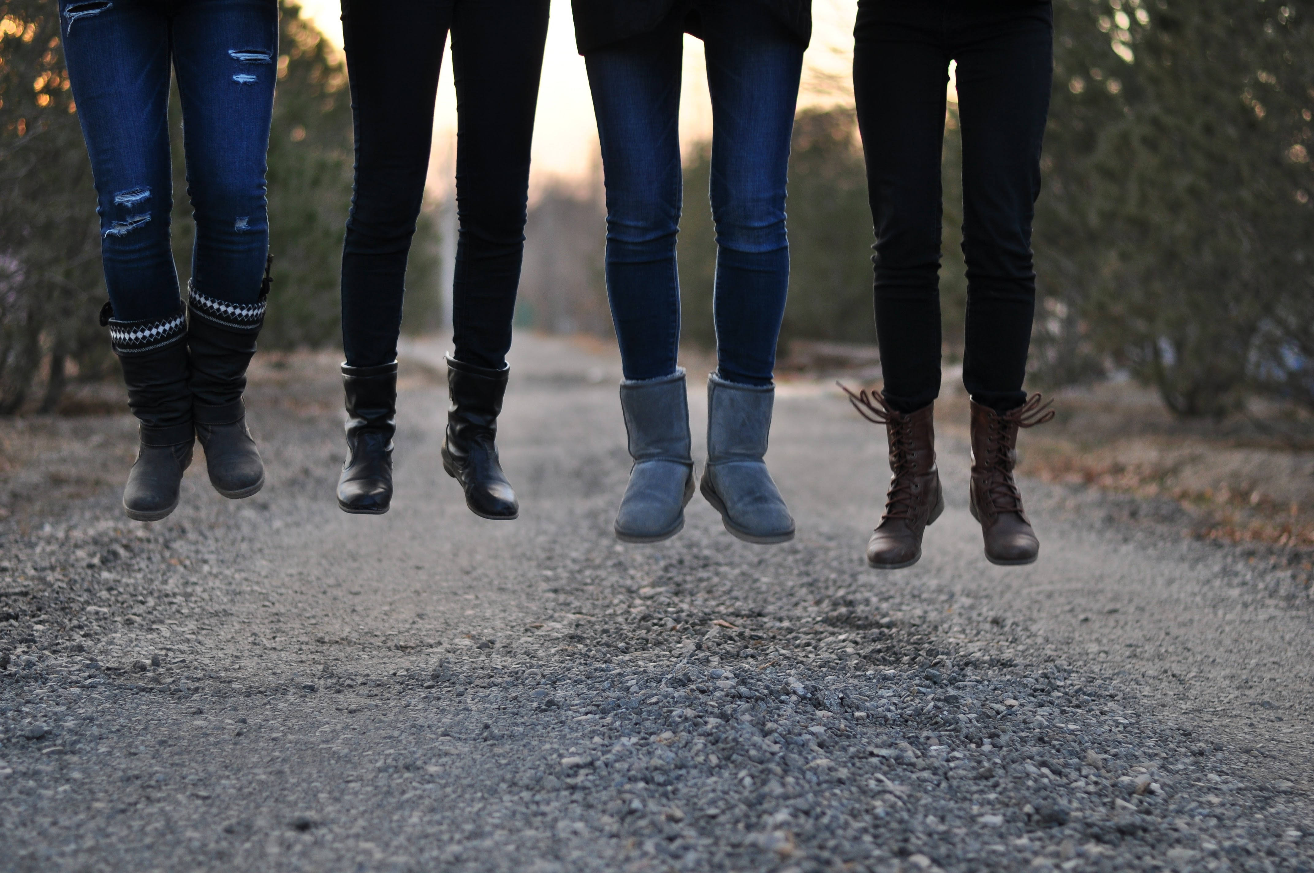 Four people jumping while wearing different types of boots