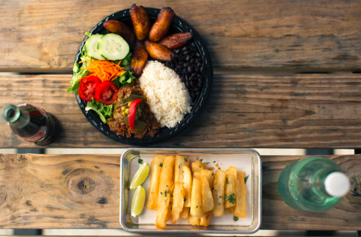 Signature platter with rice, plantains, salad, and meat.